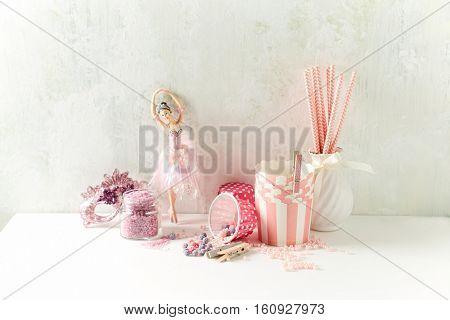 An arrangement of pink baking utensils, sugar pearls and drinking straws