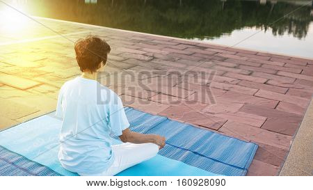 Woman meditating and yoga on a mat near a river