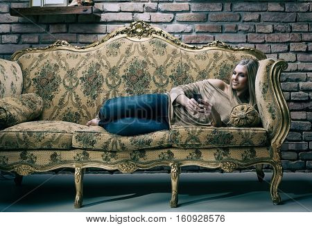 Young woman relaxing at home on baroque sofa, using mobilephone, smiling.