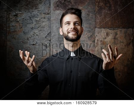 Portrait of handsome young catholic priest preaching looking up smiling.