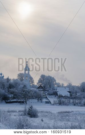 View on a village with church covered with snow on a frosty day over a small river, Porechye village, Nerl river, Tver region Russia