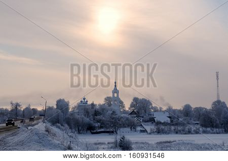 View on a village with church covered by snow on a frosty day over a small river, Porechye village, Nerl river, Tver region Russia