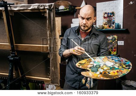 Artist looks at his painting with a brush and palette in his hands Artistic process in workroom