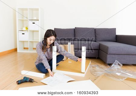 Asian woman assembling new furniture