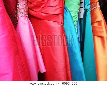 Many colours of dresses on shop rack.