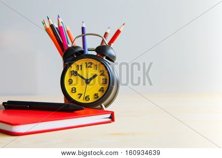 Focus on the clock on plain background laid colored pencils and diary memoirs on the wooden Background