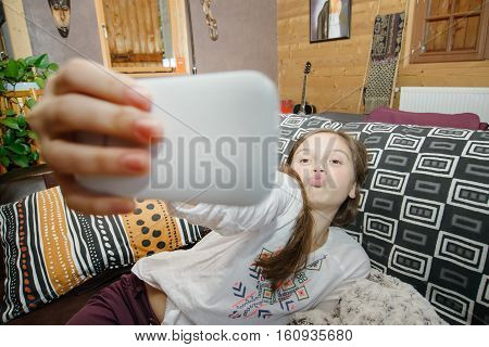 young happy teenage girl on home sofa couch taking selfie