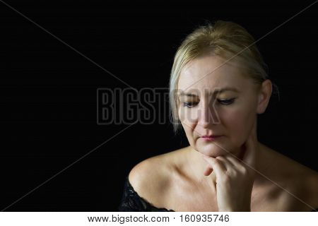 Low key portrait of pensive blond middle aged woman supporting her chin by hand. All is on a black background. Free place for your text is in the left side of the photo.