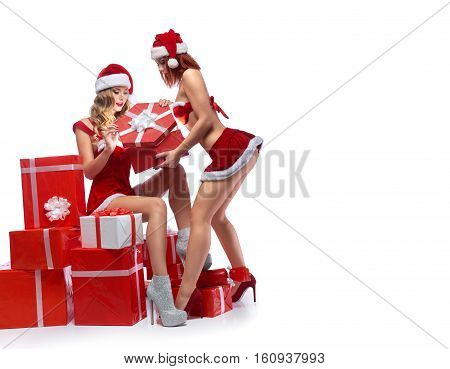 Prepare your wishes. Sexy Santa concept two hot sexy girls in Santa Claus outfits opening a magical Christmas presents isolated on white