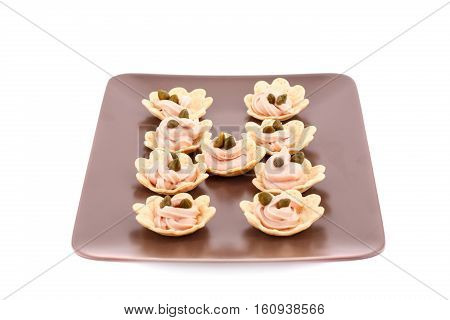 Fish cream and capers in pastries on brown plate.