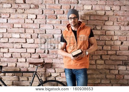 Young smart trendy caucasian man in glasses and cap standing at brick wall reading book. Copyspace for text.   .