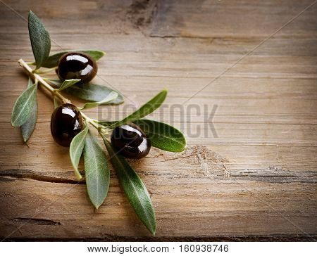 Olives And Olive Branch On A Wooden Background.