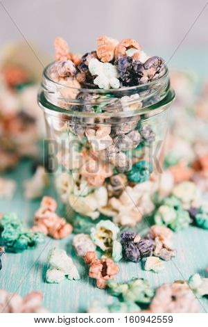 Colorful rainbow candy popcorn. Fruit flavored popcorn in glass jar. Sugared popcorn texture