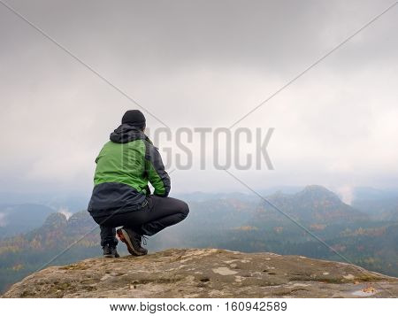 Tourist In Red Cap And In Green Black Sportswear  Squat On  Rock