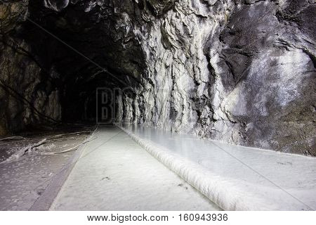 Old abandoned iron ore mine shaft tunnel with rails