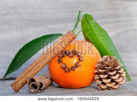 clementine with cloves in the shape of a heart and cinnamon on wooden background