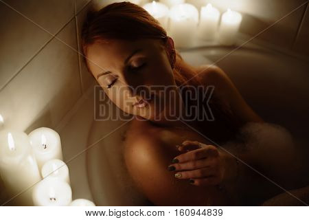 Young beautiful red-haired woman relaxes in the bath by candlelight