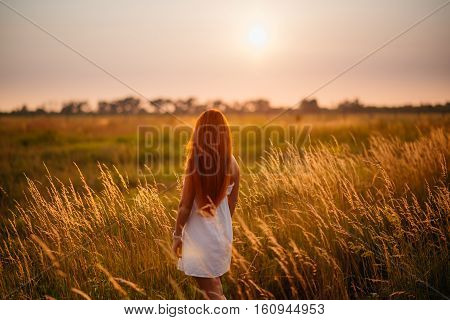 Young beautiful red-haired girl in a field at sunset back to camera facing the sun