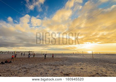 Adelaide Australia - August 16 2015: People playing volleyball at Glenelg Beach on a warm sunny evening