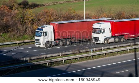 Two lorries with red trailers driving side to side on the motorway