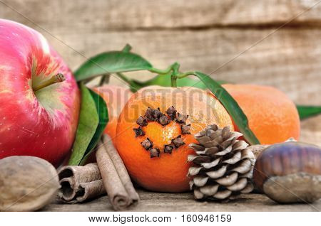 clementine with cloves in the shape of a heart apple nut and chestnut on wooden background