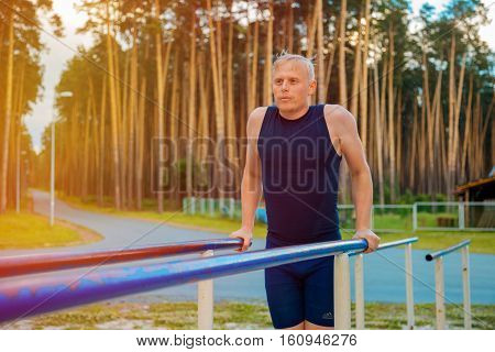 Training Outdoors. Man Doing Biceps And Triceps Dips Training On Horizontal Bars In The Sport Park.