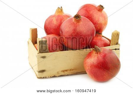 pomegranate(Punica granatum) in a wooden crate on a white background