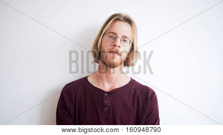 portrait of red-haired young man with beard wearing glasses