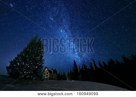 Milky Way in sky full of stars above building in winter mountains. Astro landscpe.