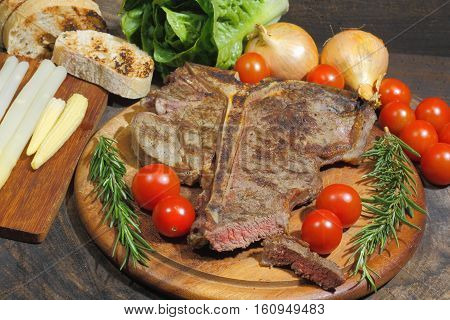 Grilled T bone steak with rosmary tomatoes corn onions and asparagus garnished on a rustic wooden chopping board