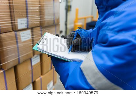Closeup shooting hand of worker with clipboard checking goods in freezing room or warehouse.Import and export management system to customer