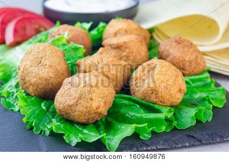Chickpea falafel balls on slate board with vegetables and sauce horizontal