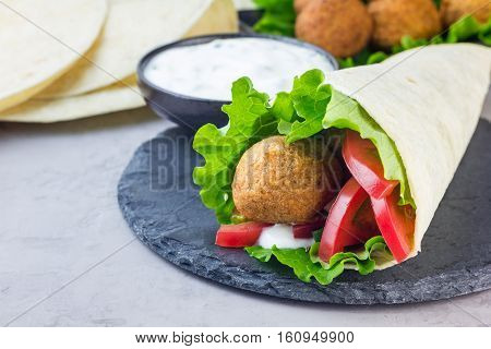 Chickpea falafel balls with vegetables and sauce roll sandwich preparation horizontal copy space