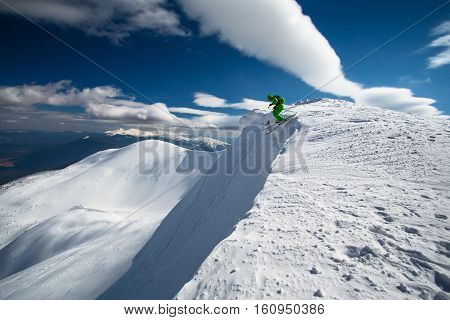 Skier jumps off mountain peak in powder snow extreme drop. Skiing in winter Carpathian mountains. Hoverla mountain on background.