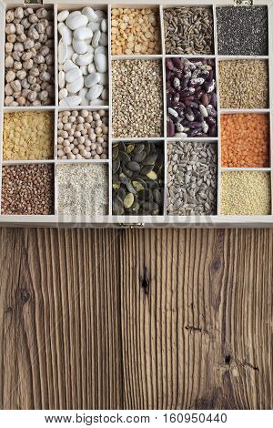 Spices and leguminous vegetables in bowls, isolated on wooden background