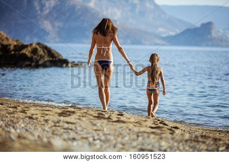 Young woman and her daughter walking on sandy beach