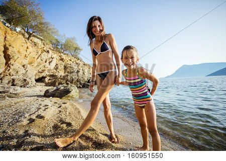 Young woman and her daughter standing at the beach