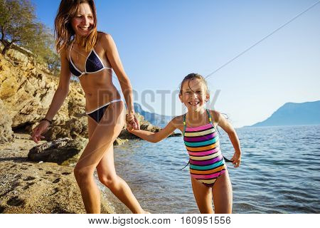 Happy young woman and her daughter walking along sandy beach
