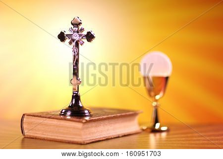 Catholic religion theme.  Holy Bible, the cross and gold chalice on stone background.