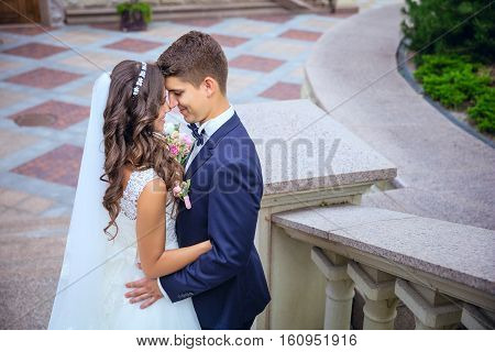 Beautiful young bride and groom going to kiss outdoors