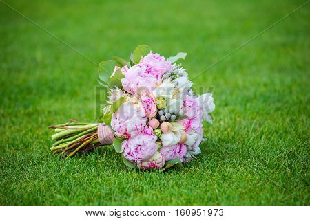 Beautiful wedding  bouquet on the green grass waiting for the bride