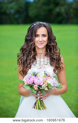 Beautiful young bride with a wedding buketomna outdoors