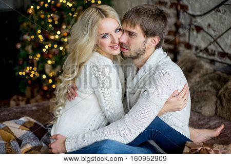 Happy Couple Of Lovers In Pullovers Look Each Other Sitting