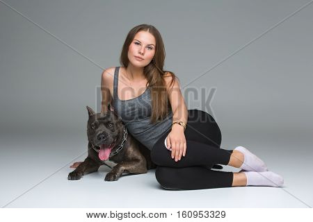 Beautiful sporty young woman sitting on floor and hugging adult grey amstafford terrier dog. Studio shot over gray background. Copy space.