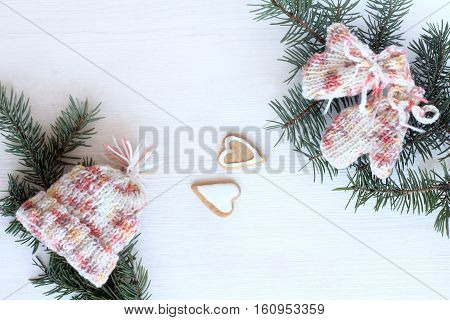 Cookies in the form of two hearts and warm knitted wardrobe items to fir twigs top view / warm favorite winter vacation