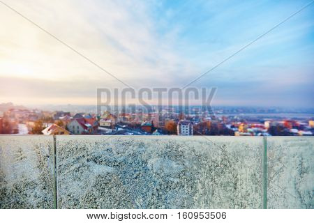 freezing outside winter cityscape through the glass banisters covered with frost