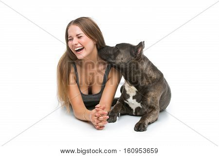 Beautiful sporty happy young woman sitting on floor and hugging adult grey amstafford terrier dog. Studio shot. Isolated over white background. Copy space.