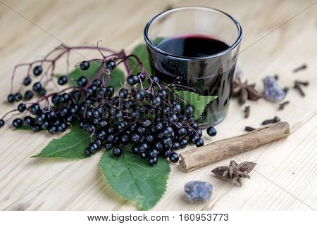 Glass of fresh elderberry syrup with cinnamon stick brown sugar star anise and elderberries on a wooden kitchen counter