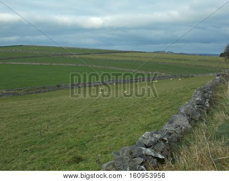 English country side scene with old dry stone wall and rolling hills into the distance