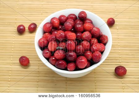 Cranberries in a round white bowl and spilled berries on brown straw mat top view closeup